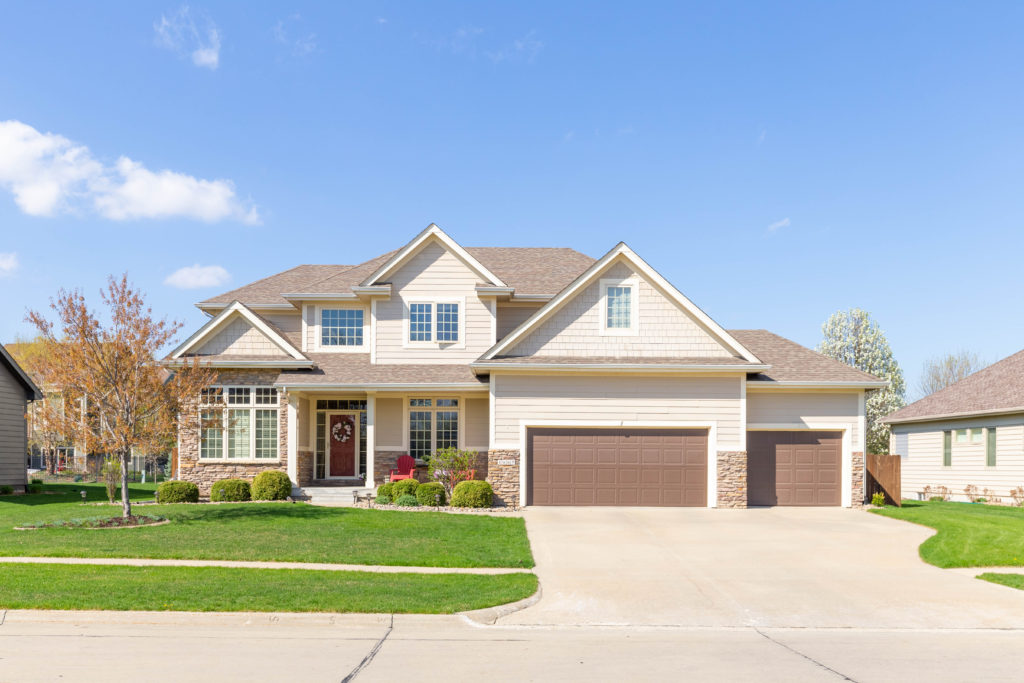 Outdoor real estate photograph of two-story house in Waukee Iowa in the spring with green grass and blue sky