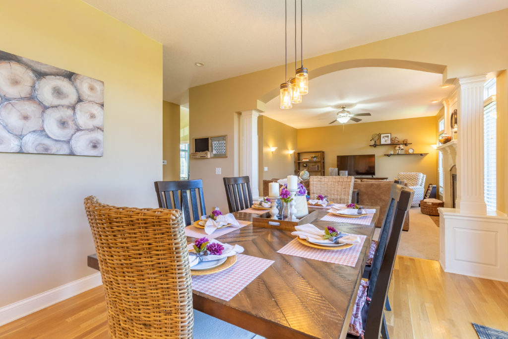 Interior real estate photograph of dining room table with living room in the background