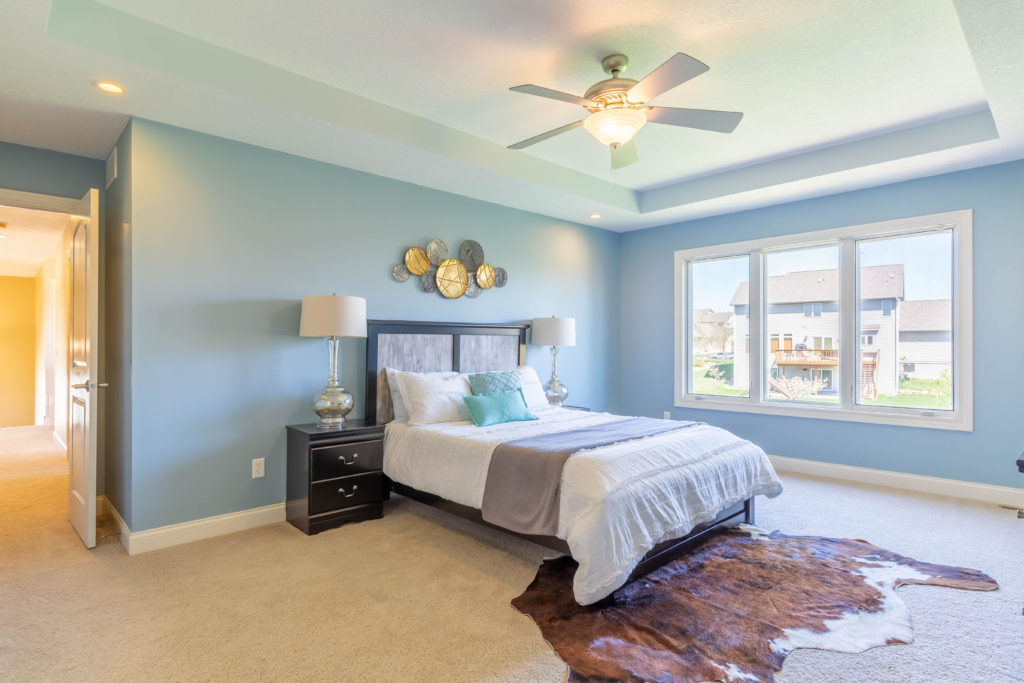 Interior real estate photograph of bedroom with light blue walls