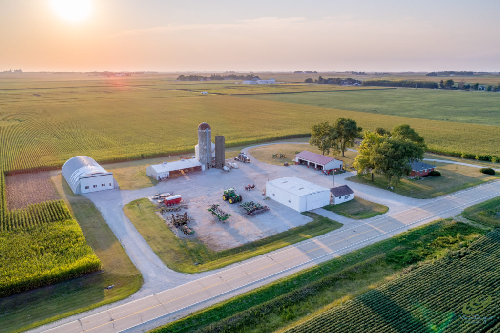 Aerial photograph of farm surrounded by corn fields at sunset in Iowa